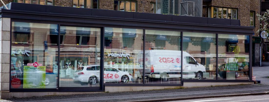 Reflektion av Saps-fordon i fönster i stadsmiljö