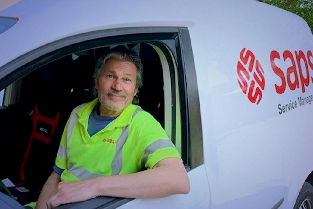 Saps medarbetare i en parkerad Saps-fordon med reflexväst