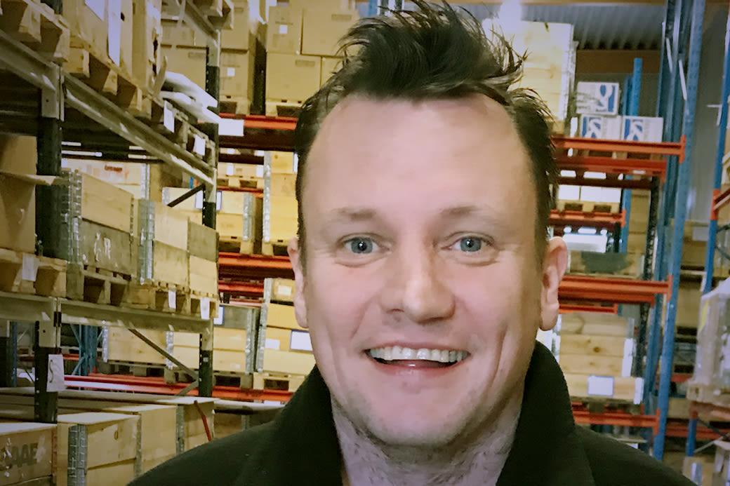 Ansikte av glad Saps anställd i lagerlokal med mycket gods