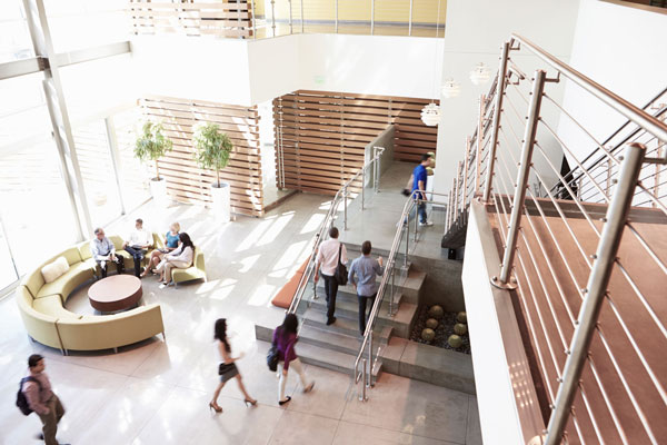 Fastighetsservice. Väntrum med två våningar och trappa. Personer i rörelse