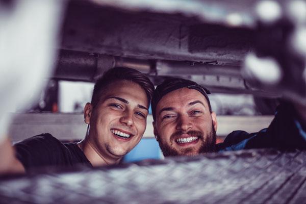 Två glada Saps medarbetare med stort leende som utför underhåll